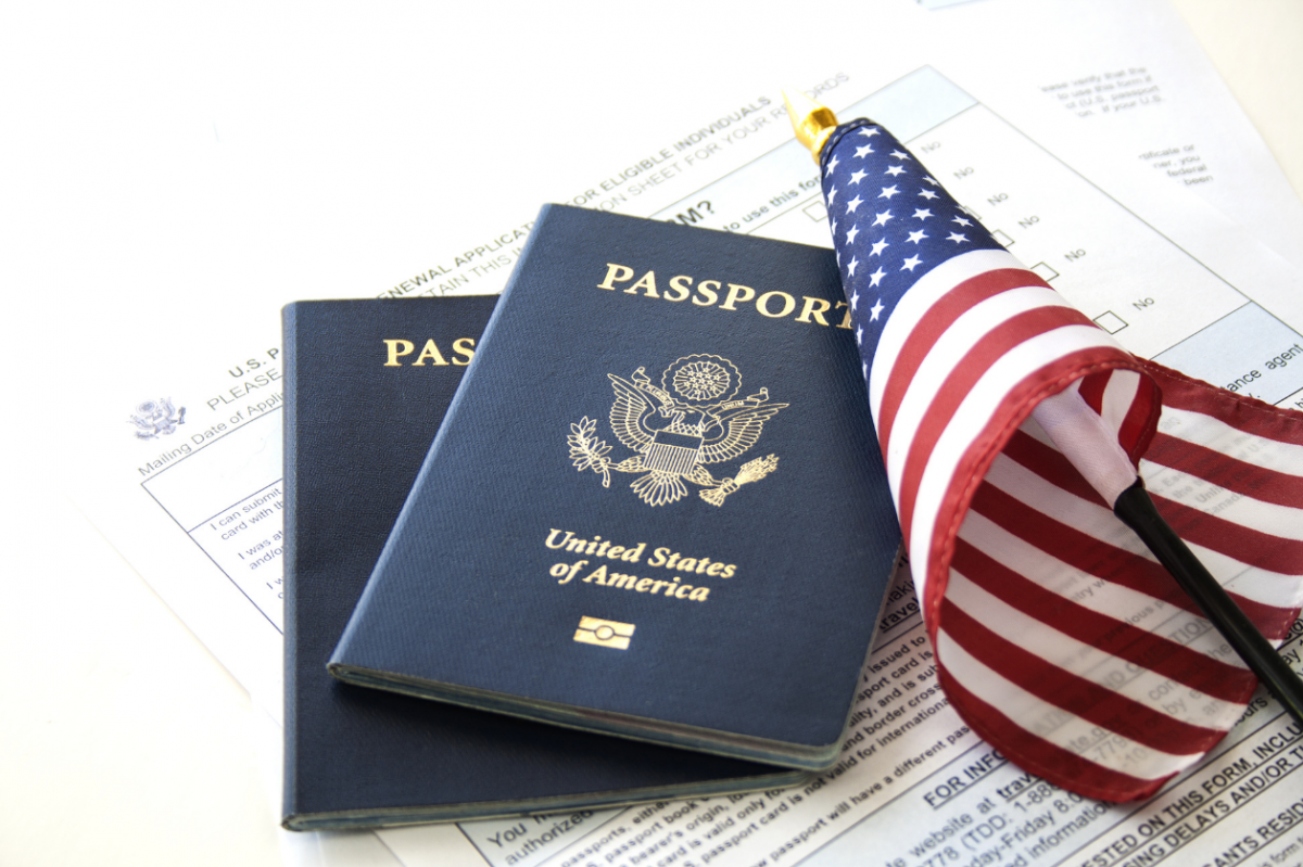 Two passports, a Visa application and a small American flag