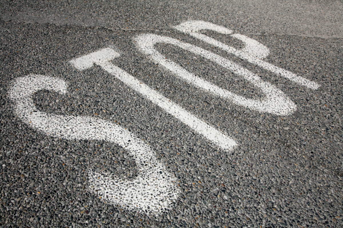 """The word """"Stop"""" written in chalk on a gravel road"""