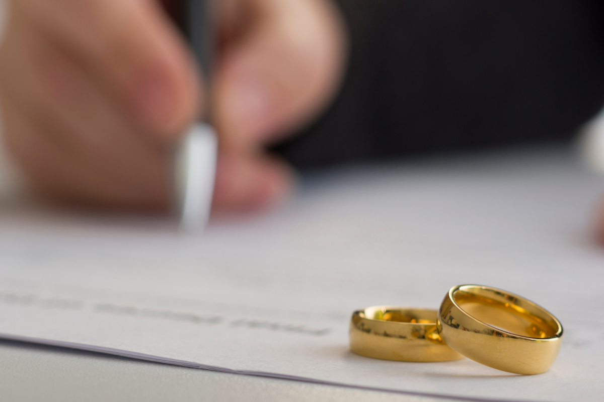 Person's hand signing divorce papers with two gold wedding rings in the foreground