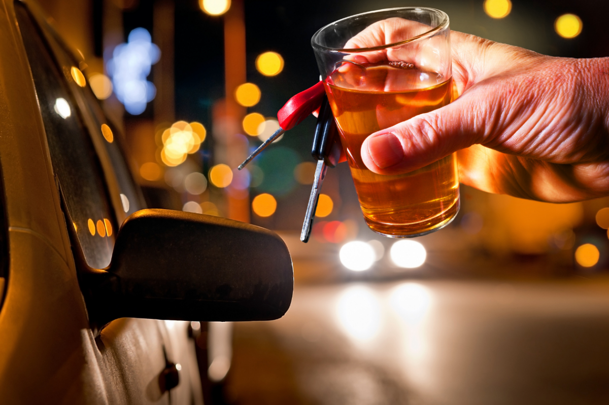 Man's hand holding glass of whiskey and car keys about to enter vehicle