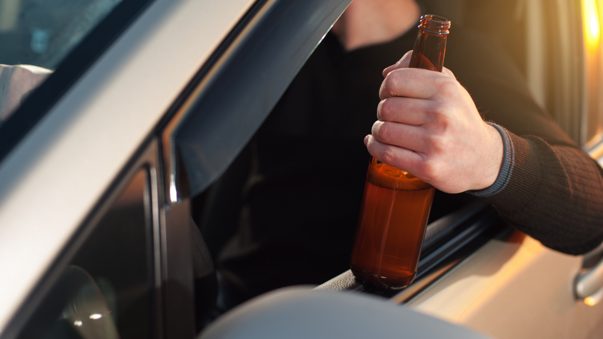 Man in car holding a half-full beer bottle out the window