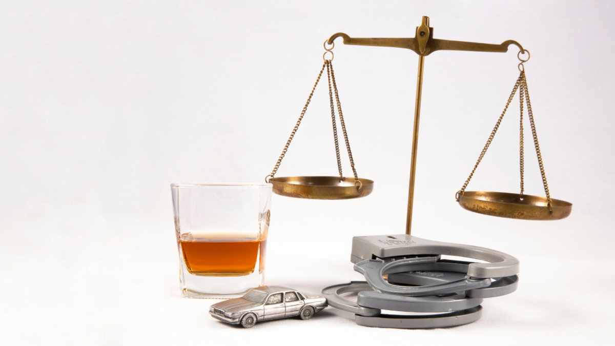 Scales of justice, handcuffs, small car and a glass of whiskey